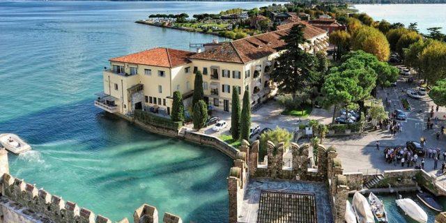 Sirmione tra il lago di Garda, il Castello Scaligero e il cartello sul bacio